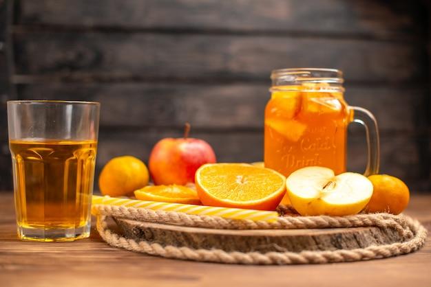 Vista anterior de jugo orgánico fresco en una botella y vaso servido con tubo y frutas sobre una tabla para cortar