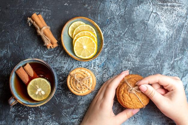 Vista anterior de limones frescos y una taza de té negro con canela mano sujetando galletas apiladas sobre fondo oscuro