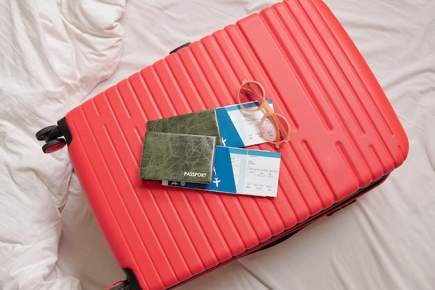 Vista anterior de maleta femenina con gafas de sol, pasaportes y billetes de avión en la cama