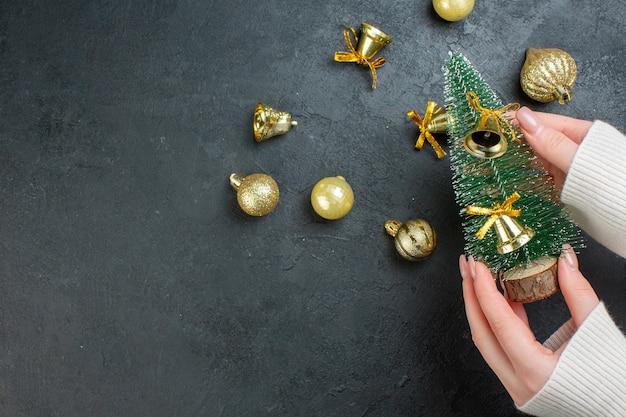 Vista anterior de la mano que sostiene el árbol de navidad y accesorios de decoración sobre fondo oscuro