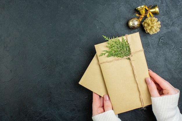 Vista anterior de la mano que sostiene cajas de regalo y accesorios de decoración sobre fondo oscuro