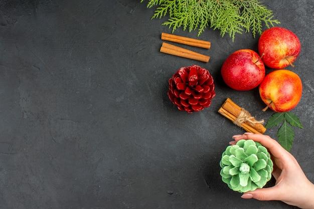 Vista anterior de manzanas frescas, canela, limones y accesorios de decoración sobre fondo negro