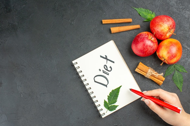 Vista anterior de manzanas frescas orgánicas naturales con hojas verdes, canela, limas, cuaderno con inscripción de dieta sobre fondo negro