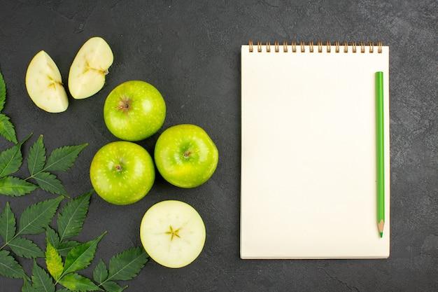 Vista anterior de manzanas verdes frescas enteras y picadas y menta junto al cuaderno con lápiz sobre fondo negro