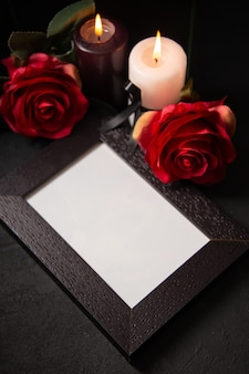 Vista anterior del marco de imagen con flores rojas sobre una superficie oscura