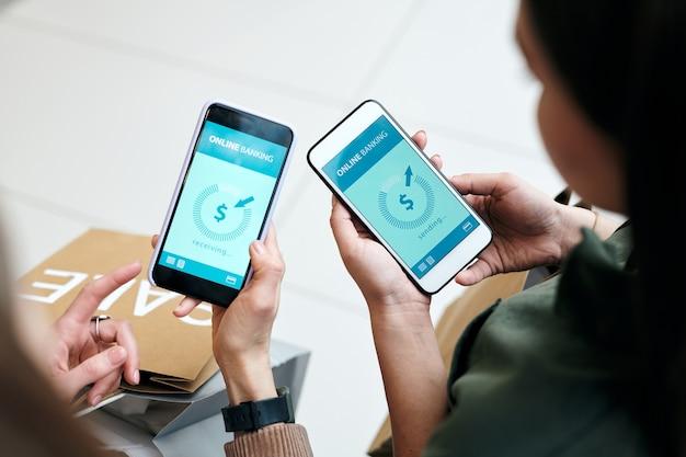 Vista anterior de la mujer enviando dinero a un amigo en línea mediante un banco móvil en un gadget, haciendo compras juntos