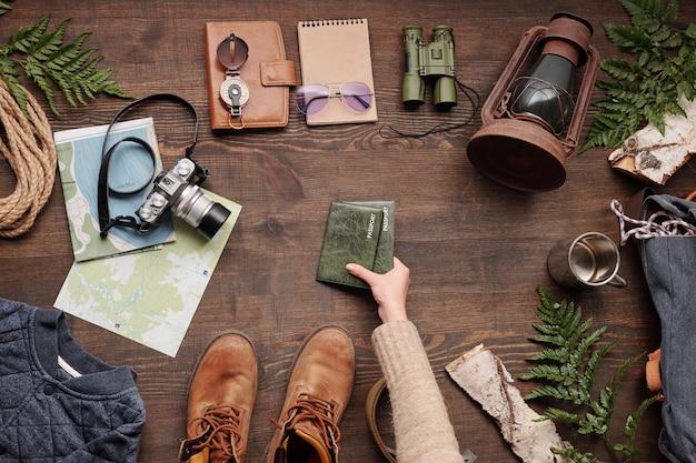 Vista anterior de la mujer que toma los pasaportes en cubiertas verdes de la mesa de madera