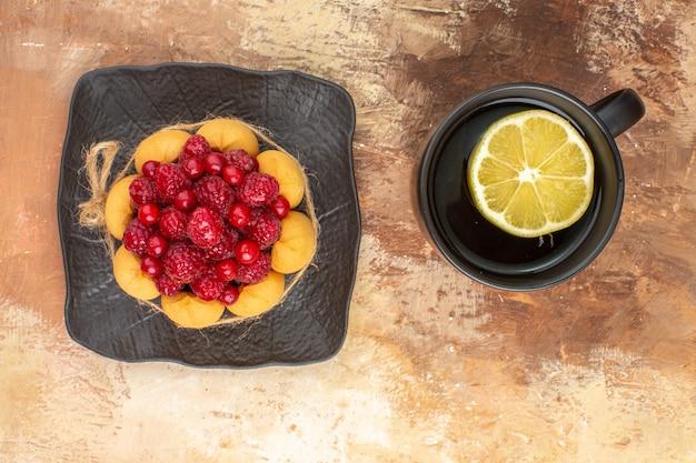 Vista anterior de un pastel de regalo con frambuesas y una taza de té con limón en una bandeja marrón