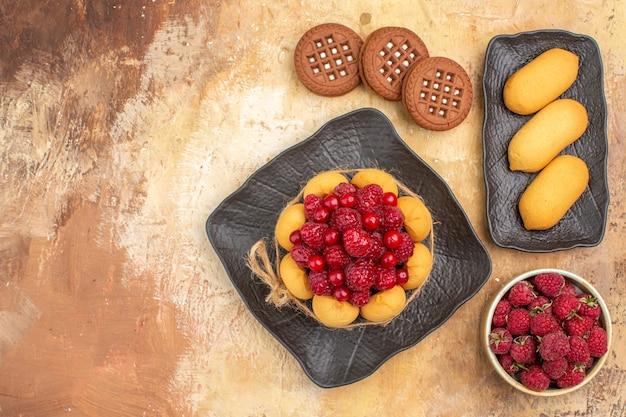 Vista anterior de un pastel de regalo y galletas en placas marrones en la tabla de colores mezclados