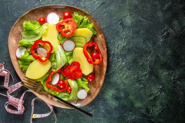 Vista anterior de patatas cortadas peladas frescas con pimiento rojo rábanos tomates verdes tenedor en una placa marrón y metros sobre la superficie de colores mezcla verde negro