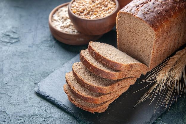 Vista anterior de rebanadas de pan negro, harina, avena, trigo sarraceno, sobre placa de color oscuro sobre fondo azul angustiado