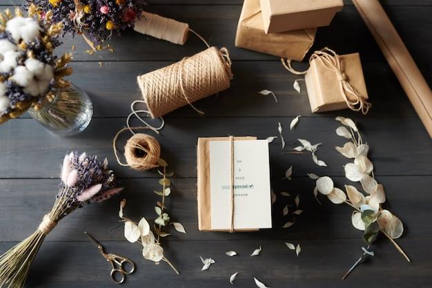 Vista anterior de regalos empaquetados en la mesa con pétalos desordenados, tijeras, cordel, pila de cajas de regalo y flores secas
