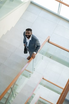 Vista anterior del sonriente joven empresario afroamericano con barba llevando maletín y subiendo escaleras en el centro de la oficina