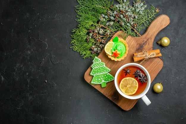 Vista anterior de una taza de té negro accesorios navideños cono de coníferas y limones de canela sobre una tabla de cortar de madera sobre fondo negro