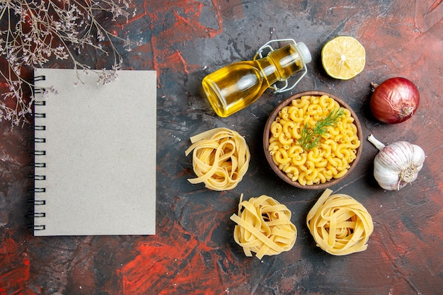 Vista anterior de tres porciones crudas de espaguetis y pastas de mariposa en un recipiente marrón y una botella de aceite de ajo y limón con cebolla verde junto al cuaderno en la tabla de colores mezclados