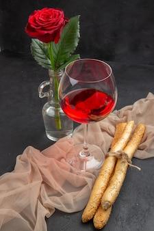 Vista anterior de vino tinto en una copa de cristal sobre una toalla sobre fondo negro