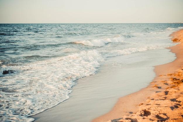 Vista de la arena de la playa con olas del mar y filtro de espuma blanca