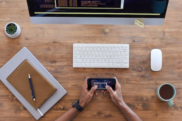 Vista de arriba hacia abajo en manos masculinas sosteniendo el teléfono inteligente sobre el lugar de trabajo contemporáneo con computadora y taza de café en la mesa de madera con textura, espacio de copia