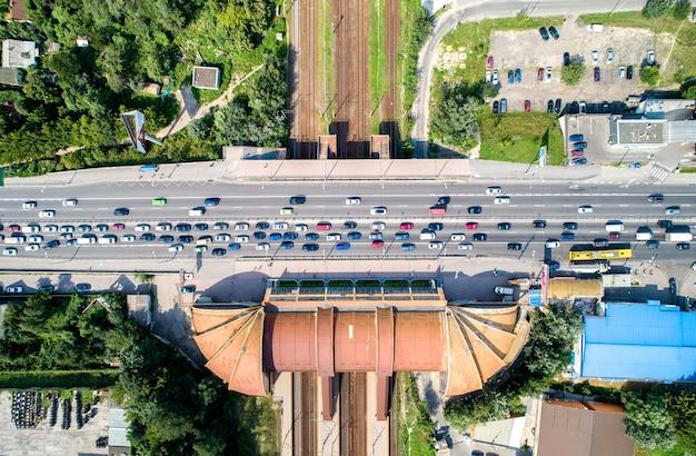 Vista de arriba hacia abajo de un puente de carretera que cruza una vía férrea. estación karavaevi dachi - kiev, ucrania