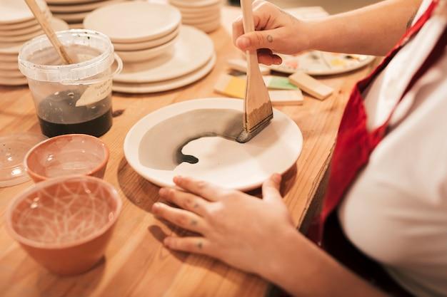 Una vista desde arriba de la artesana femenina pintando el plato con pincel