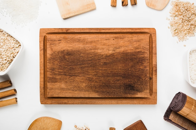 Una vista desde arriba de la bandeja de madera vacía con espátula; arroz; palitos de canela sobre fondo blanco