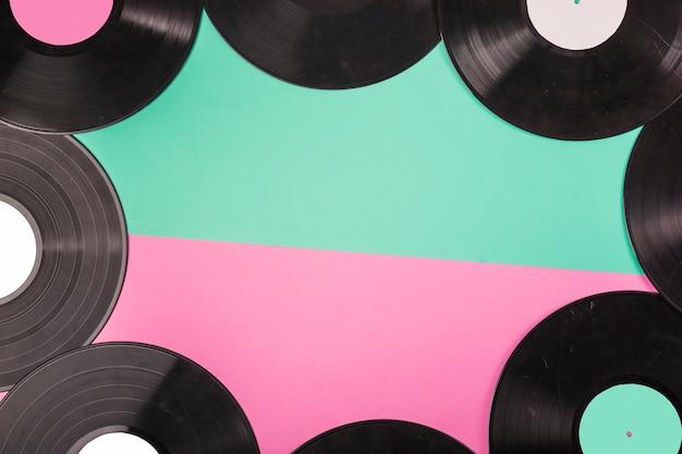 Una vista desde arriba del borde de los discos de vinilo sobre doble fondo verde y rosa