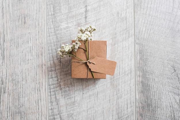 Una vista desde arriba de la caja de cartón atada con etiquetas y flores de aliento de bebé en el escritorio de madera