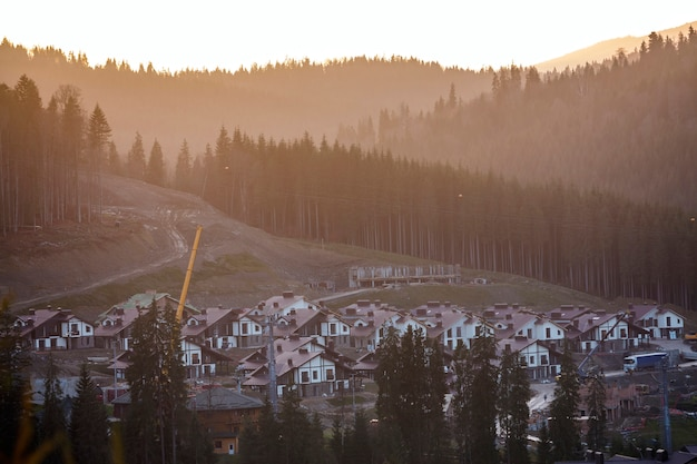Vista desde arriba de la ciudad turística de cabaña en el valle de montaña entre hermosos y altos pinos siempre verdes
