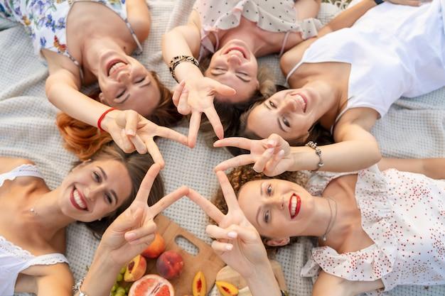 Vista desde arriba. la compañía de hermosas novias se divierte y disfruta de un picnic al aire libre.