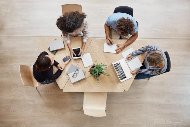 Vista desde arriba. concepto de negocio, startup, trabajo en equipo. socios principiantes sentados en el espacio de coworking hablando sobre proyectos futuros, mirando ejemplos de trabajo en computadoras portátiles y tabletas digitales.