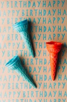Vista de arriba del cono de helado vacío azul y rojo en el papel del regalo del feliz cumpleaños