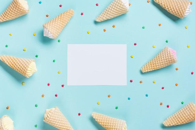 Una vista desde arriba de los conos de galleta y rociados rodeados cerca del papel blanco en blanco sobre fondo azul