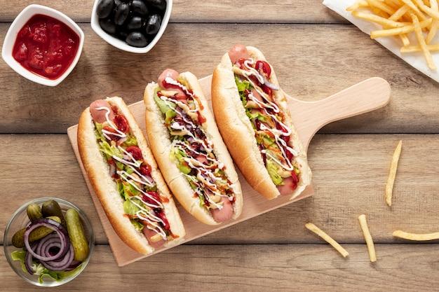 Vista de arriba decoración con hot dogs y tabla de cortar