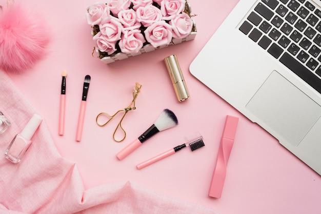 Vista de arriba decoración con laptop sobre fondo rosa