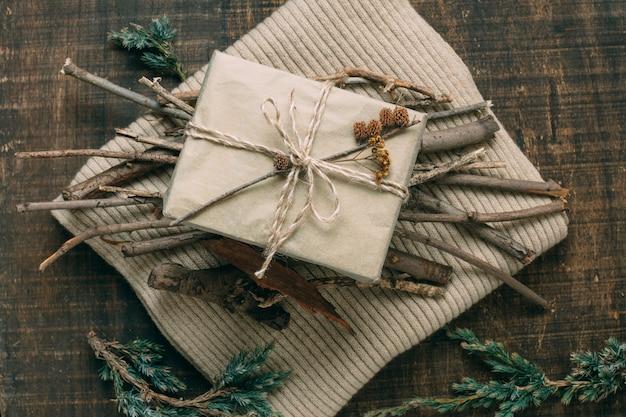 Vista de arriba decoración con regalo y ramitas en suéter