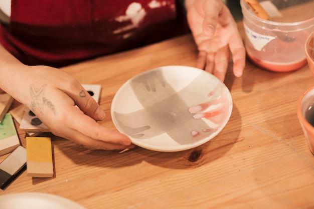 Una vista desde arriba del decorador de cerámica femenino que sostiene una placa de cerámica pintada