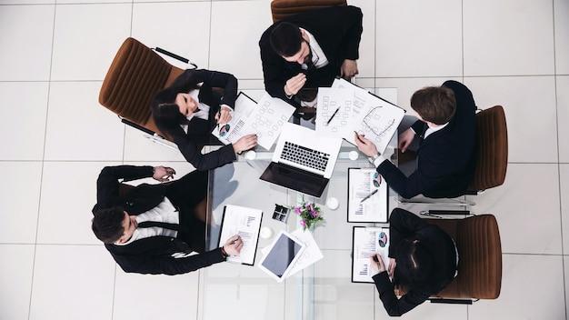 Vista desde arriba: el director ejecutivo y el equipo empresarial en una reunión de trabajo en una oficina moderna.