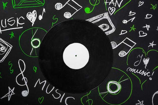 Una vista desde arriba del disco de vinilo sobre la pizarra con notas musicales dibujadas
