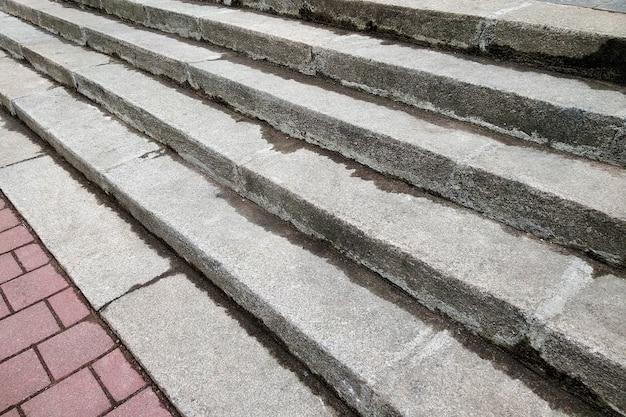 Vista desde arriba de las escaleras de hormigón gris que conducen al pavimento colorido al aire libre en un día soleado.