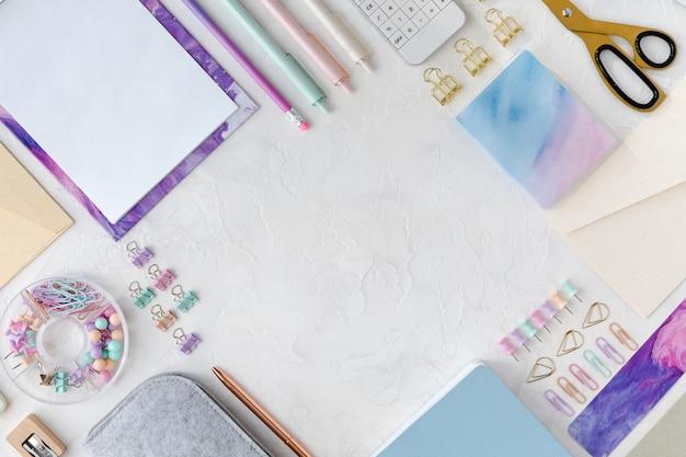 Vista desde arriba de flatlay de papelería en el fondo de la tabla blanca.