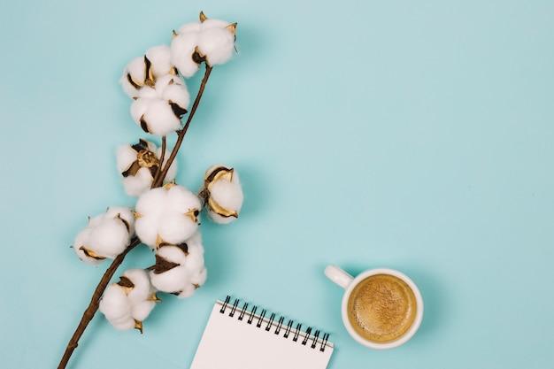 Una vista desde arriba de la flor de algodón; bloc de notas espiral y taza de café sobre fondo azul
