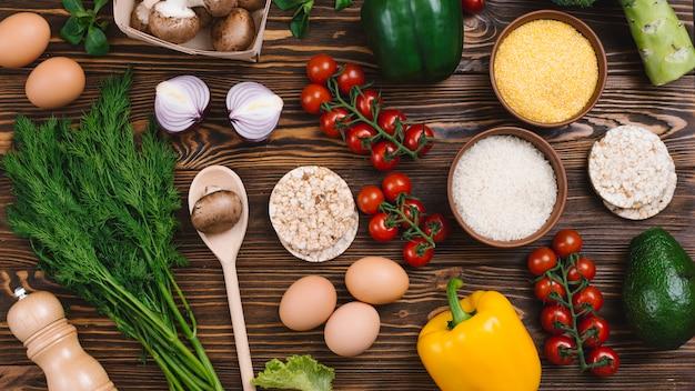 Una vista desde arriba de los granos de arroz; polenta; pastel de arroz inflado y verduras en mesa de madera
