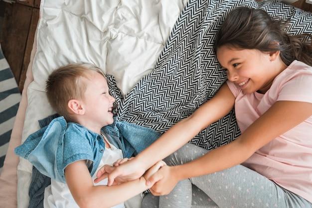 Una vista desde arriba del hermano y la hermana sonrientes burlándose en la cama