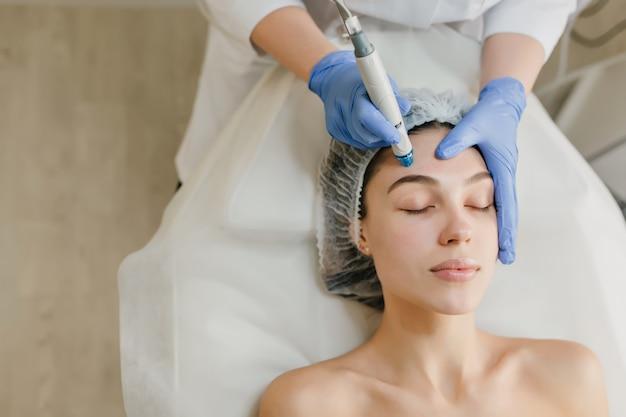 Vista desde arriba de hermosa mujer disfrutando de procedimientos de cosmetología, rejuvenecimiento en salón de belleza. dermatología, médico en el trabajo, asistencia sanitaria, terapia, botox.