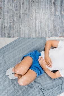 Una vista desde arriba de un hombre que usa un calcetín acostado en la cama sufriendo de dolor de estómago