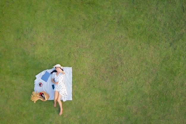Vista desde arriba de la joven mujer delgada en vestido blanco tendido relajante con ordenador portátil y café en el fondo de la hierba verde