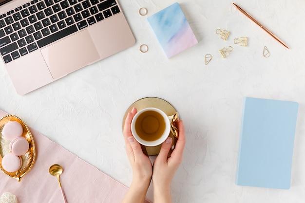 Vista desde arriba del lugar de trabajo empresarial de mujer con teclado de computadora, cuaderno, ramo de flores de peonía rosa y teléfono móvil, endecha plana.