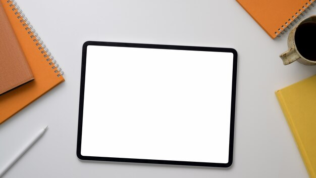 Vista desde arriba del lugar de trabajo con tableta, material de oficina y taza de café en la mesa blanca