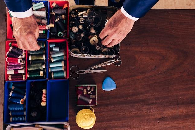 Una vista desde arriba de la mano del diseñador de moda masculino que sostiene el carrete de hilo y botones de la caja en el escritorio de madera