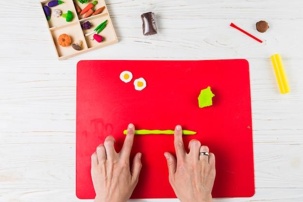 Vista de arriba de la mano humana haciendo frutas y vegetales en forma de arcilla.